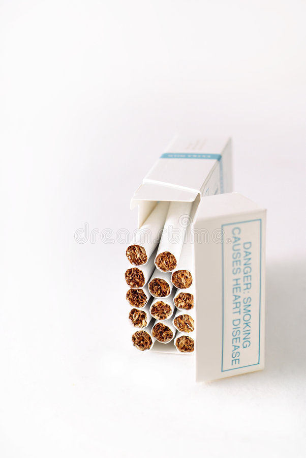 Cigarette warning. Box of cigarettes with heart disease health warning stock photos
