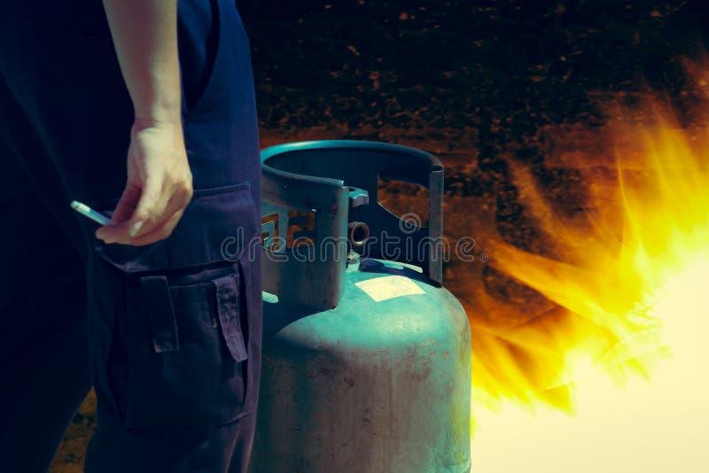 Cigaretten i hand nära cylindern för gasbehållaren kan tändning av flammab royaltyfri bild