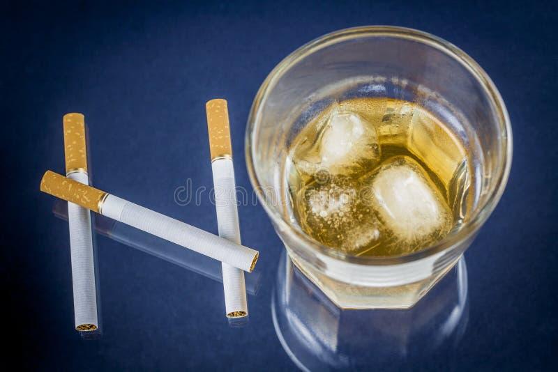 Cigaretter och exponeringsglas av alkohol som bildar det INGET ordet royaltyfria foton