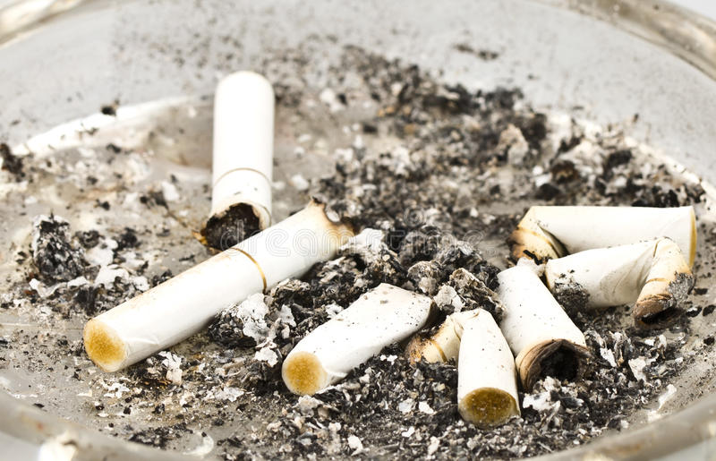 Cigarettes and ashes in an ashtray stock images