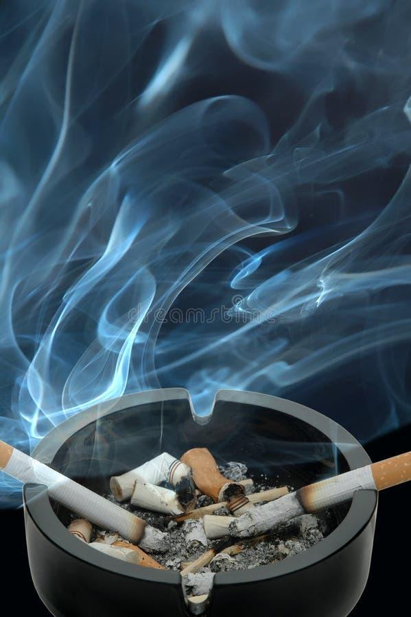 Cigarettes brûlantes dans un cendrier photographie stock libre de droits