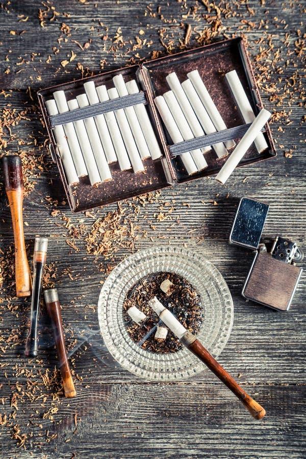 Cigarettes, cendrier et un tuyau de tabagisme images libres de droits