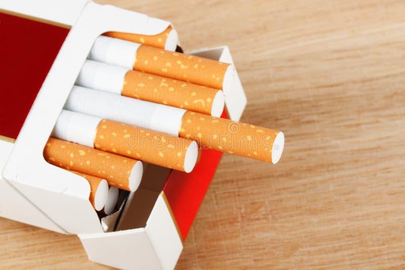Cigarettes dans le paquet sur la planche à pain photo stock