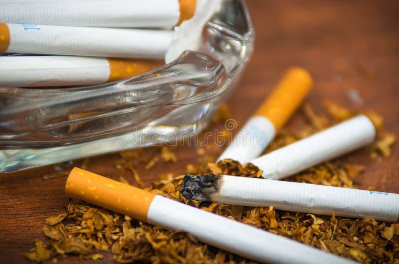 Cigarettes et tabac de plan rapproché se trouvant à l'intérieur et autour du plateau de cendre en verre sur la surface en bois, c photographie stock