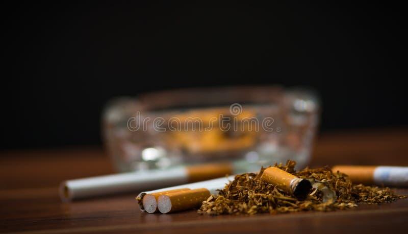 Cigarettes et tabac de plan rapproché se trouvant à l'intérieur et autour du plateau de cendre en verre sur la surface en bois, c photos libres de droits