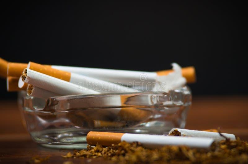 Cigarettes et tabac de plan rapproché se trouvant à l'intérieur et autour du plateau de cendre en verre sur la surface en bois, c images stock