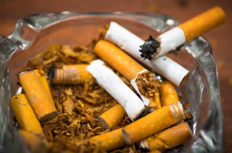 Cigarettes et tabac se trouvant à l'intérieur et autour du plateau de cendre en verre sur la surface en bois, vue d'en haut, conc photo stock
