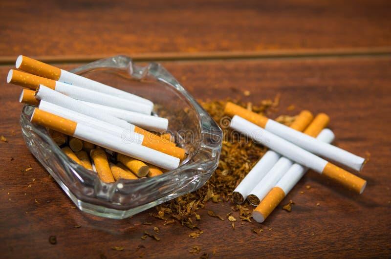 Cigarettes et tabac se trouvant à l'intérieur et autour du plateau de cendre en verre sur la surface en bois, vue d'en haut, conc photo libre de droits