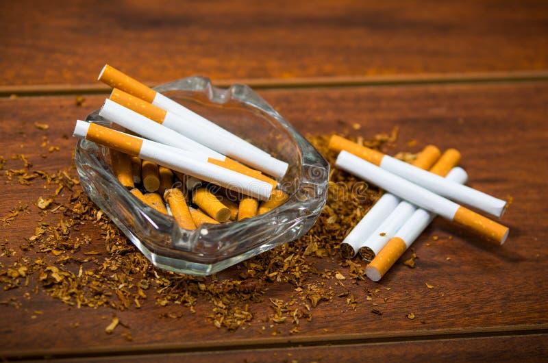 Cigarettes et tabac se trouvant à l'intérieur et autour du plateau de cendre en verre sur la surface en bois, vue d'en haut, conc photos libres de droits