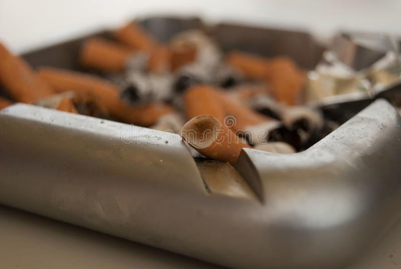 Cigarettes in grey ashtray on the table.  royalty free stock images