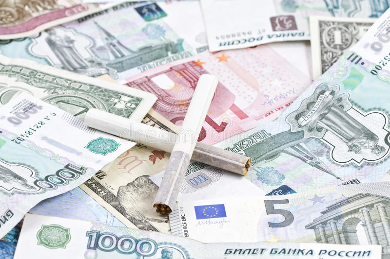Cigarettes lying on the money. Two cigarettes lying on the money stock photos
