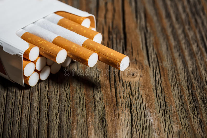 Cigarettes. Open pack of cigarettes on old wooden table stock image