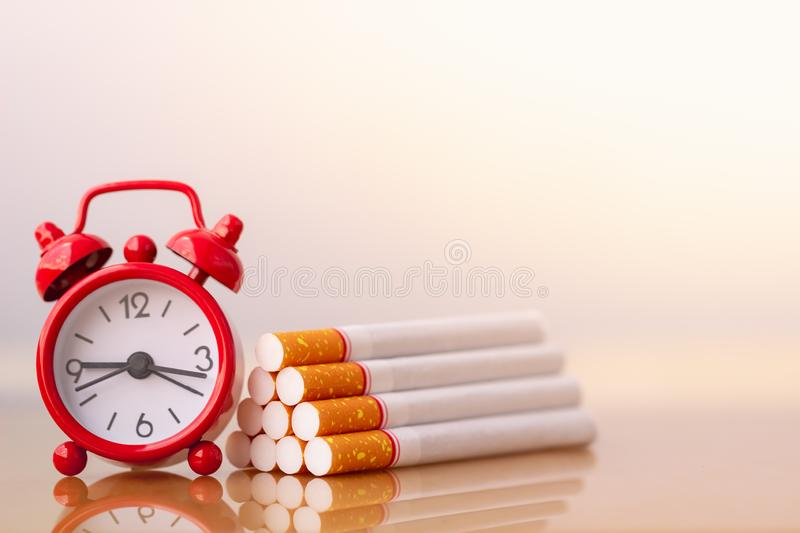 Cigarettes stack and red alarm clock. World no tobacco day. Cigarette and family figure. A concept for stop smoking. Smoking a cigarette can kill everyone in stock images