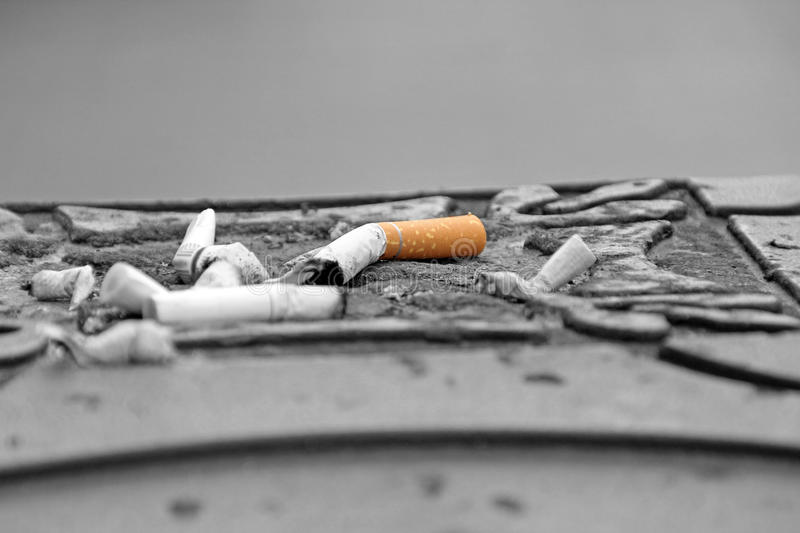 Cigarettes in street ashtray. Photo of used cigarettes stubbed out in a street ashtray stock photography