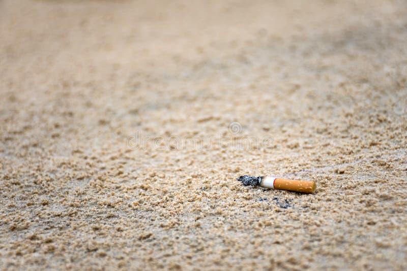 Cigarettstumpkastet på sanden av människan i stranden är det orsak av avskräde i havet och miljöbelastning royaltyfri foto