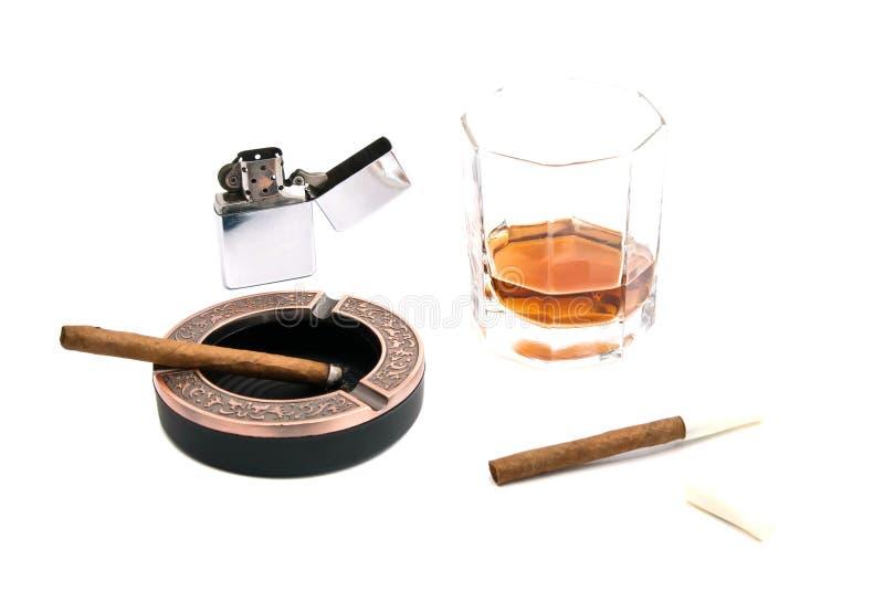 Cigarillos, cendrier, allumeur et whiskey photos stock