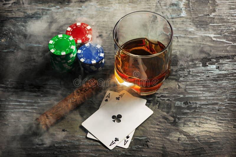 Cigarr chiper för dobblerier, drink och spelakort arkivbild