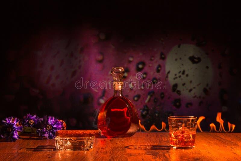 Cigarr och whisky i ett exponeringsglas med is royaltyfri fotografi