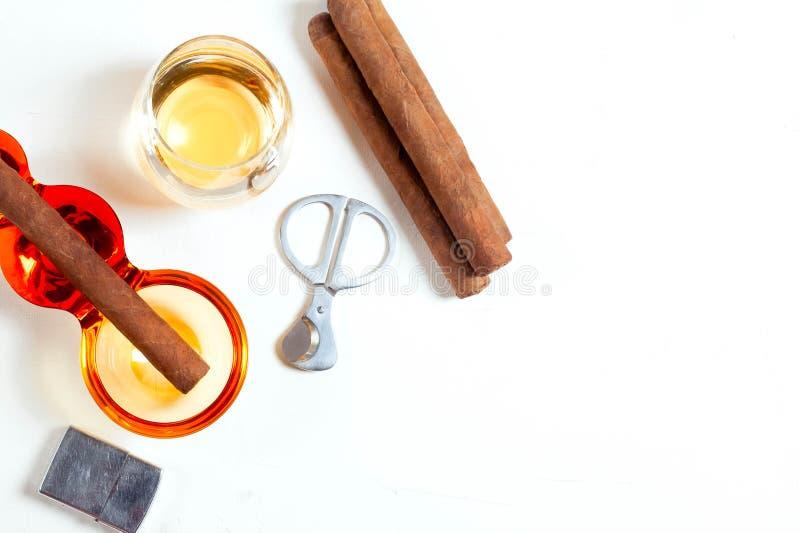 Cigarren askfatet, cigarett scissors, ljusare whiskyexponeringsglasvit royaltyfria bilder