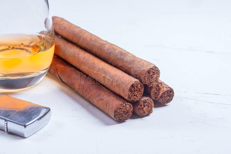 Cigarren askfatet, cigarett scissors, ljusare whiskyexponeringsglasvit fotografering för bildbyråer
