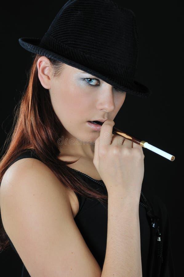 Cigarrillo agradable del asimiento de la muchacha fotografía de archivo libre de regalías