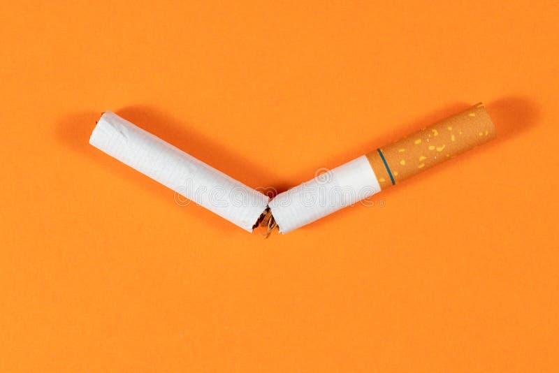 Cigarrillo del tabaco roto cerca para arriba con el fondo anaranjado imagenes de archivo