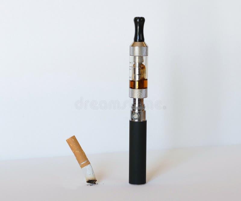Cigarrillo electrónico con el cigarrillo extinguido del tabaco imagen de archivo