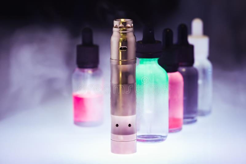 Cigarrillo electrónico con el e-líquido en el humo blanco en una oscuridad fotos de archivo libres de regalías
