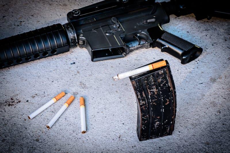 cigarrillo en arma de revista imagen de archivo