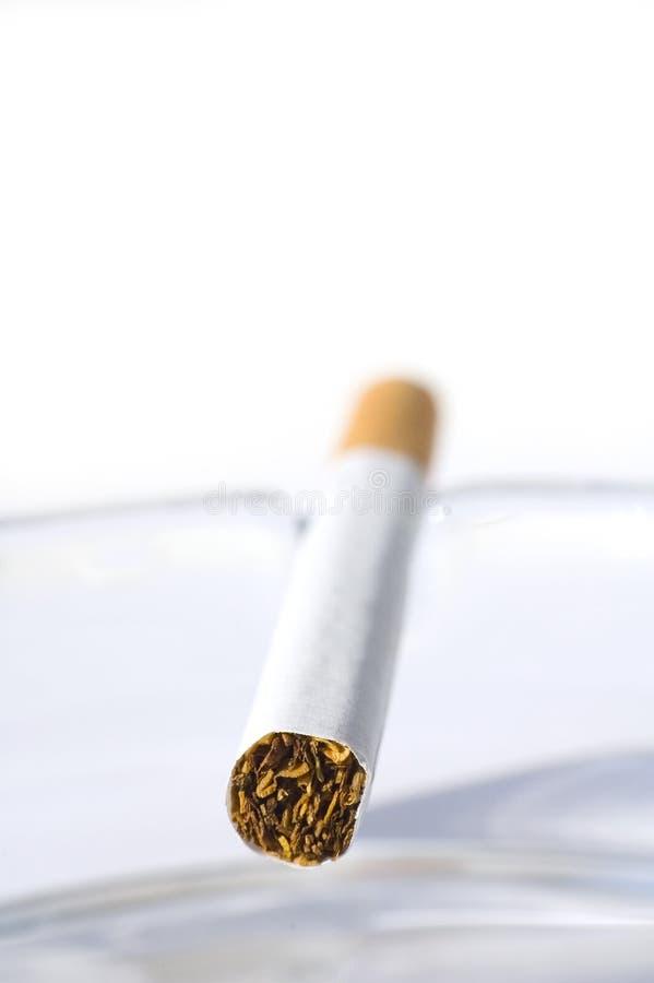 Cigarrillo en bandeja de ceniza imagenes de archivo