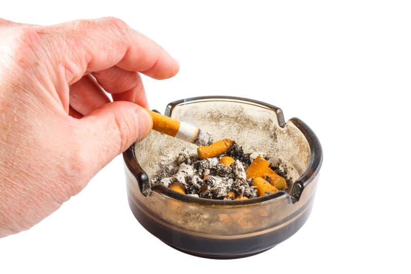 Cigarrillo en cenicero en el fondo blanco imágenes de archivo libres de regalías