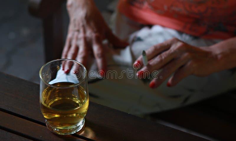Cigarrillo que fuma de la mujer y tener bebida de la vodka imagenes de archivo