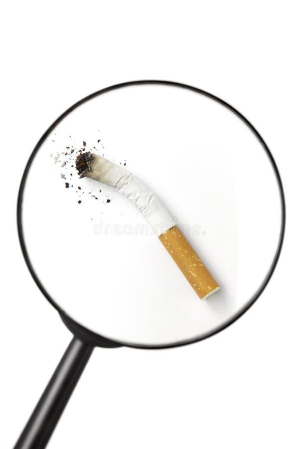Cigarrillo visto a través de la lupa imagen de archivo