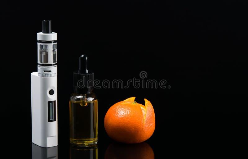 Cigarrillo y líquido electrónicos con gusto anaranjado, en un fondo negro foto de archivo