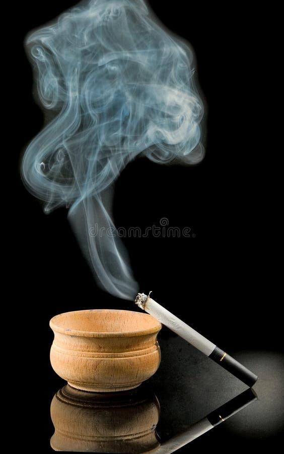 Cigarrillos y cenicero en un fondo negro fotos de archivo