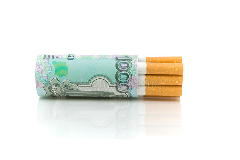 Cigarrillos y dinero en un primer blanco del fondo fotografía de archivo
