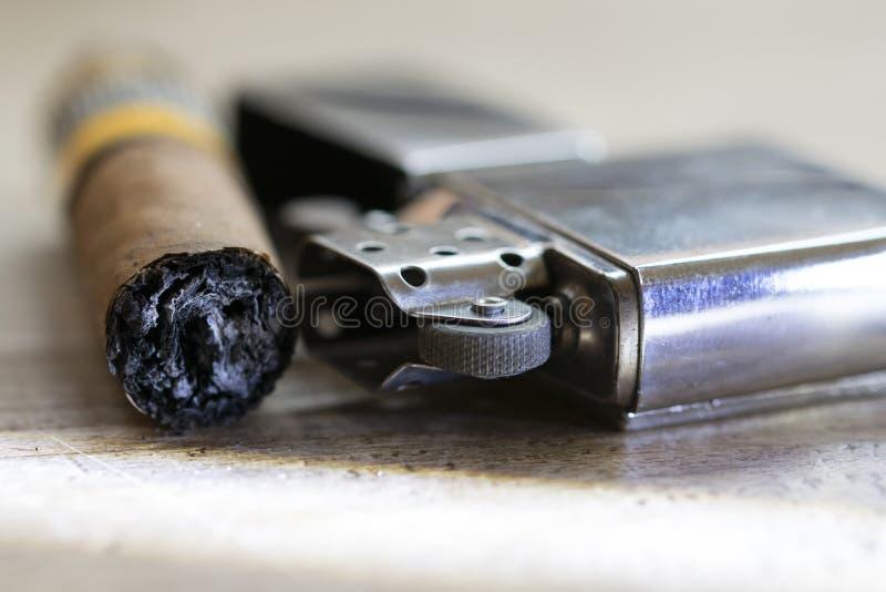 Cigarro apenas ahumado y encendedor de la gasolina foto de archivo libre de regalías