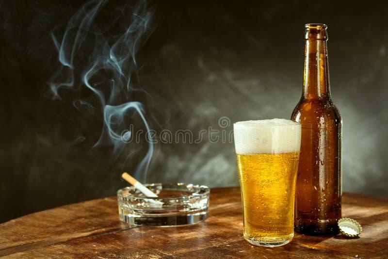 Cigarro ardente e cerveja fria em um bar imagem de stock