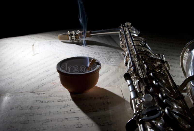 Cigarro do saxofone e música de folha velha fotos de stock