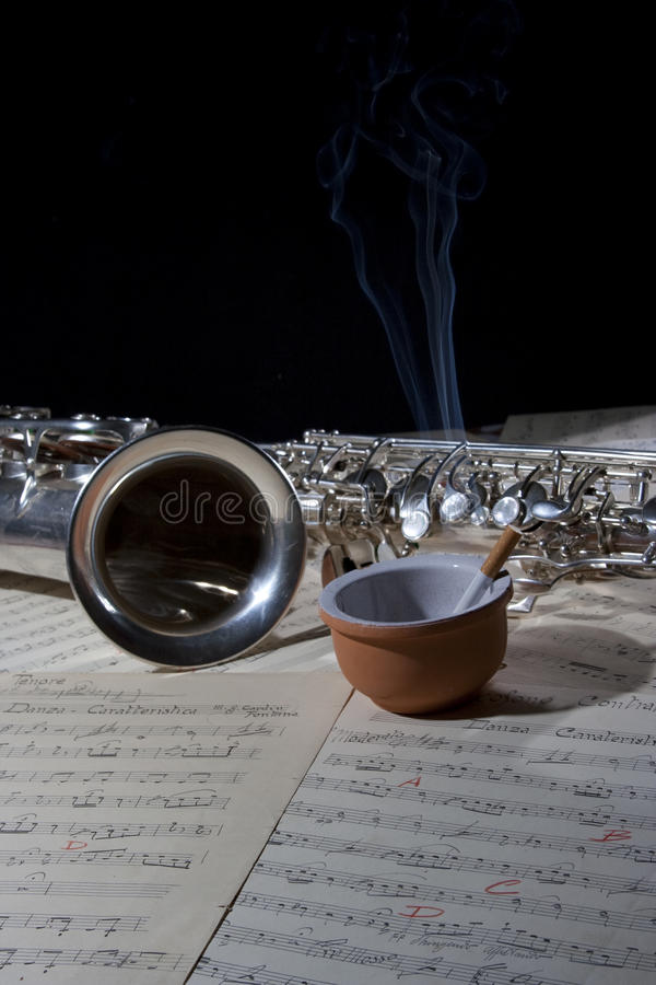 Cigarro do saxofone e música de folha velha imagem de stock