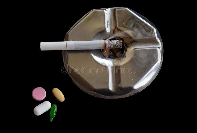 Cigarro iluminado em um cinzeiro ao lado dos comprimidos da medicina imagem de stock royalty free