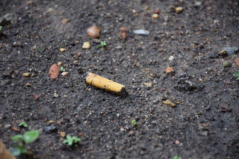 Cigarro/lixo na terra fotos de stock royalty free