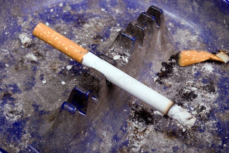 Cigarro na bandeja de cinza suja fotos de stock