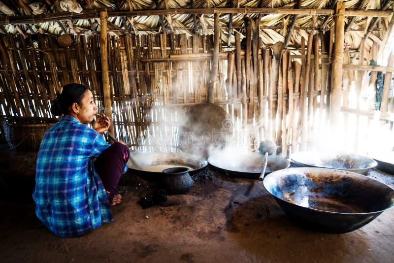 Cigarro que fuma de la mujer birmana y cocinar el azúcar de la palma en una choza cerca de Bagan, Myanmar fotografía de archivo libre de regalías
