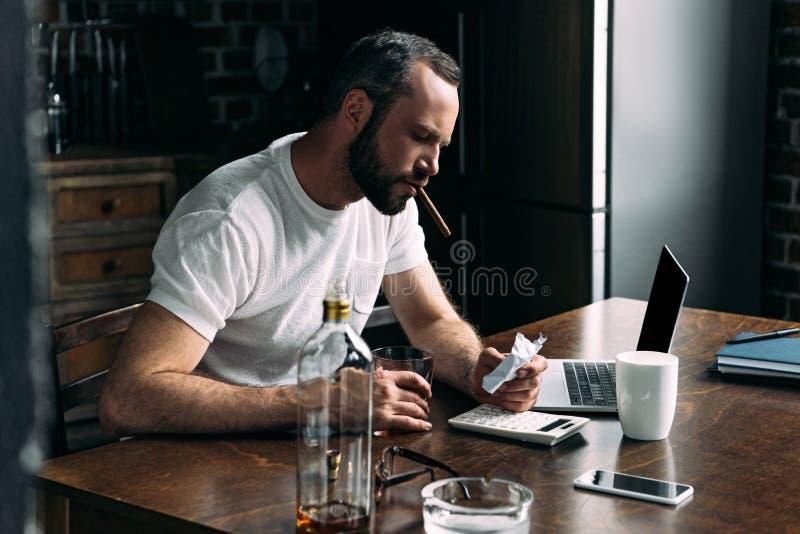 cigarro que fuma deprimido del hombre joven y mirada de la foto arrugada de la exnovia fotos de archivo libres de regalías