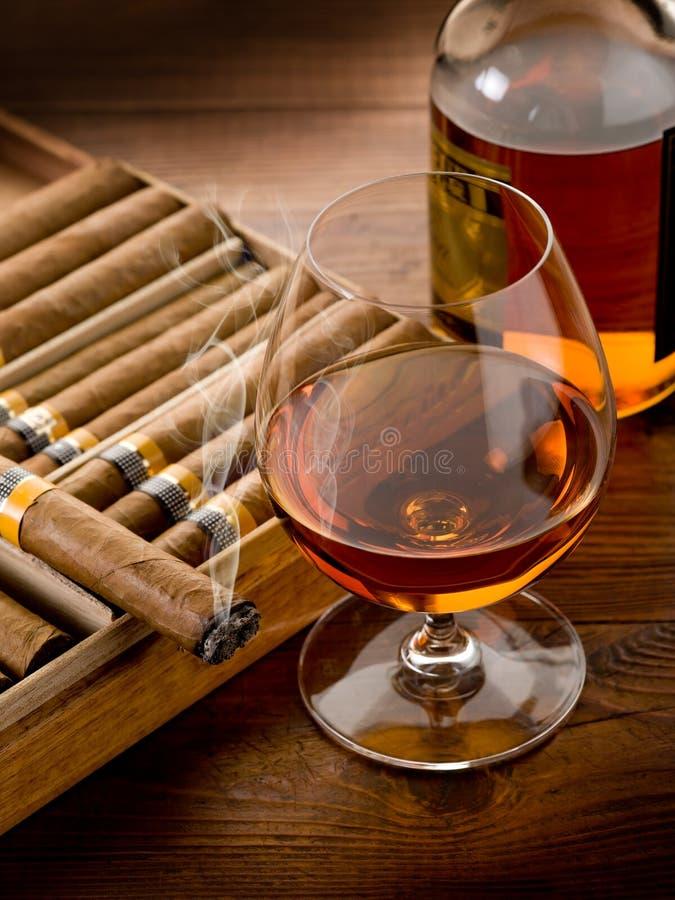 Cigarro y botella cubanos de coñac fotografía de archivo libre de regalías