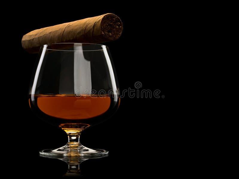 Cigarro y coñac en un vidrio fotografía de archivo