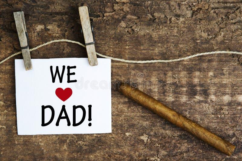 Cigarro y la muestra blanca con las palabras amamos al papá fotos de archivo libres de regalías