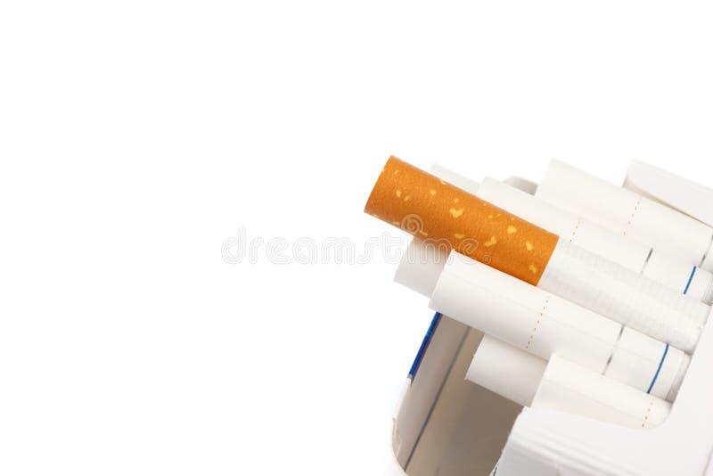 Cigarros com filtro branco em um bloco, isolado no fundo branco Close-up imagem de stock royalty free