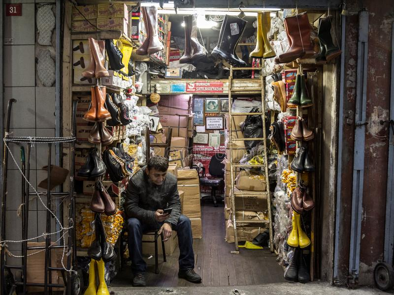 Cigarros de fumo do vendedor turco na frente do seu loja, vendendo sapatas e botas, perto do bazar da especiaria fotografia de stock